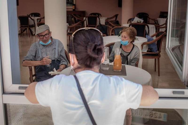 Una mujer conversa con sus padres a través de una ventana habilitada en la residencia de mayores Ballesol Patacona, en Valencia. EFE