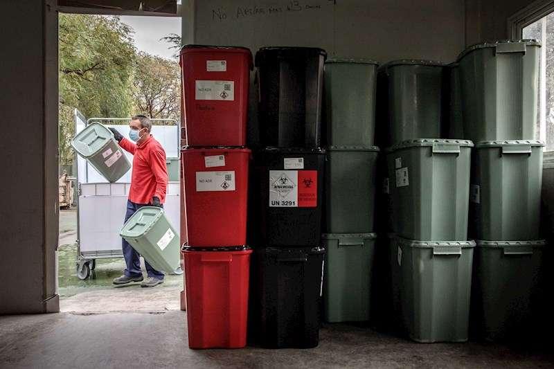 Un trabajador de la Oficina Verde de gestión de residuos del Hospital General de València, almacena residuos peligrosos de pacientes con coronavirus. EFE